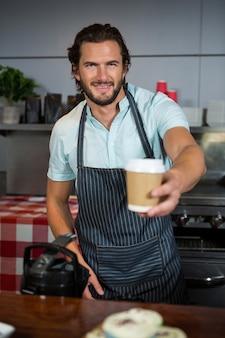 Personal masculino que sirve taza de café desechable en el mostrador