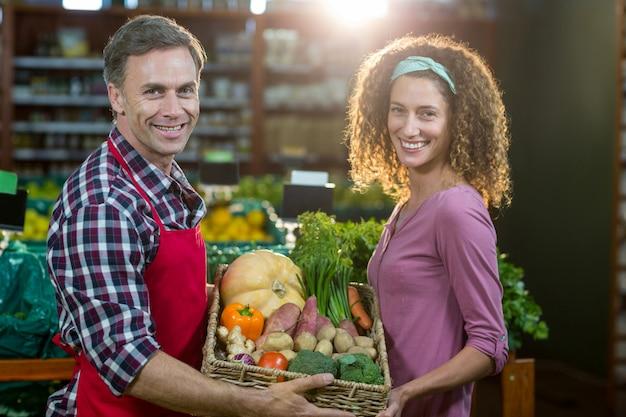 Personal masculino sonriente ayudando a una mujer con compras