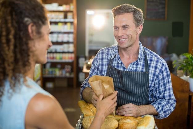 Personal masculino sonriente dando pan embalado a mujer