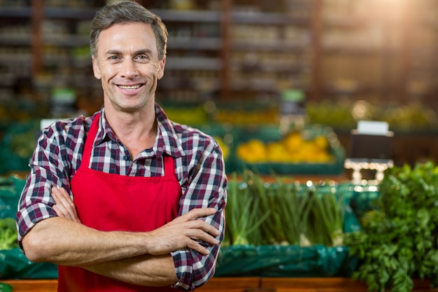 Personal masculino sonriente de pie con los brazos cruzados en la sección orgánica