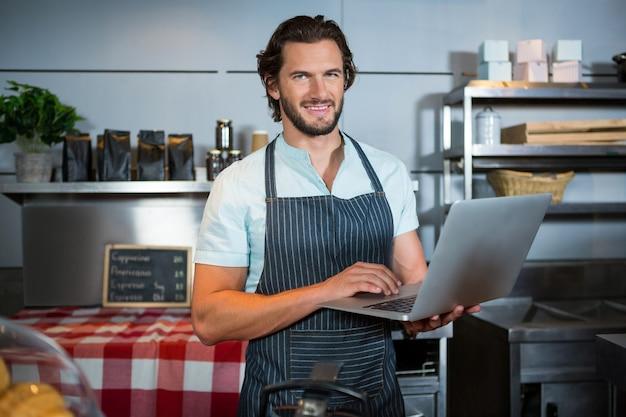 Personal masculino sonriente con portátil en el mostrador