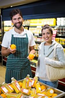 Personal masculino sonriente que ayuda a una mujer con compras