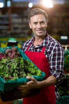 Personal masculino sonriente sosteniendo una caja de verduras frescas en el supermercado