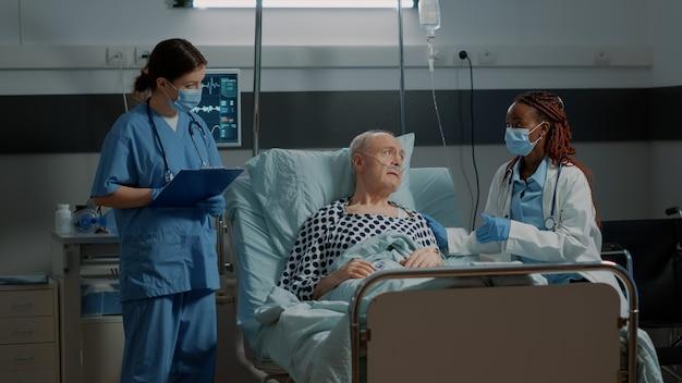 Personal médico multiétnico que supervisa la salud del paciente.