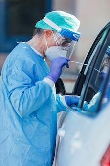 El personal médico que usa un epp, realiza pcr con un hisopo en la mano, a un paciente dentro de su automóvil para detectar si está infectado con covid-19