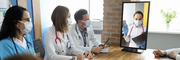El personal médico se sienta a la mesa con documentos y mira el monitor en el que el médico ve la conversación.