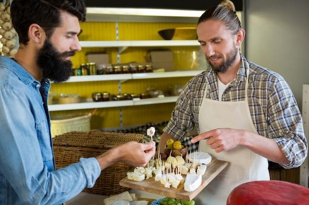 Personal mostrando una muestra de queso al cliente en el mostrador