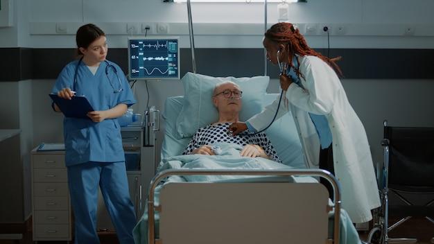 El personal multiétnico trata al paciente en la sala del hospital