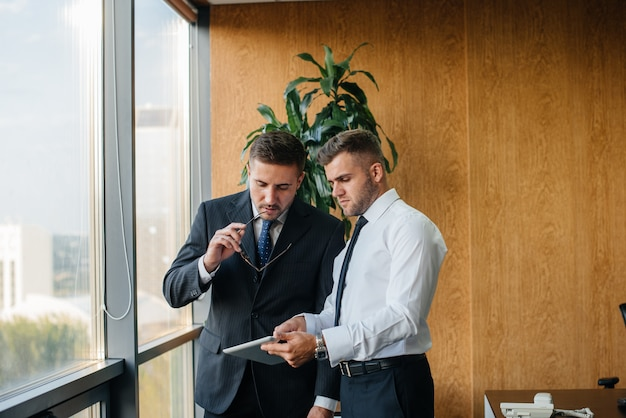 El personal de la oficina para discutir asuntos de negocios al lado de la ventana. financiación de las empresas