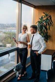 El personal de la oficina para discutir asuntos de negocios al lado de la ventana. financiación de las empresas.