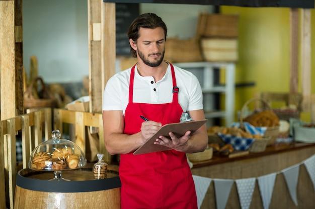 Personal de panadería escribiendo en el portapapeles en el mostrador