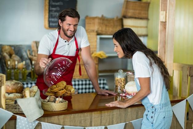 Personal de panadería mostrando bocadillos a la clienta en el mostrador
