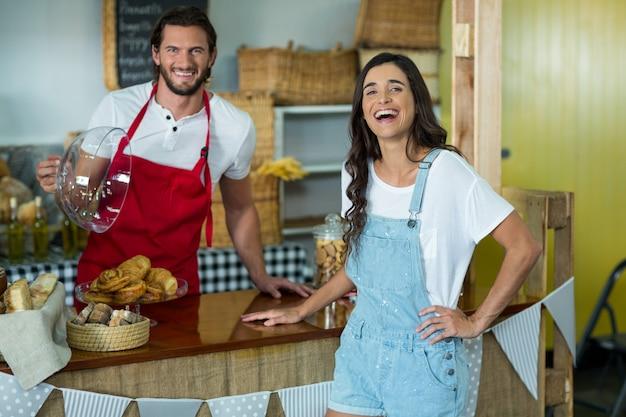 Personal de panadería sonriente mostrando bocadillos a la clienta en el mostrador