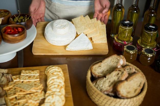Personal de pie cerca de varios quesos en el mostrador