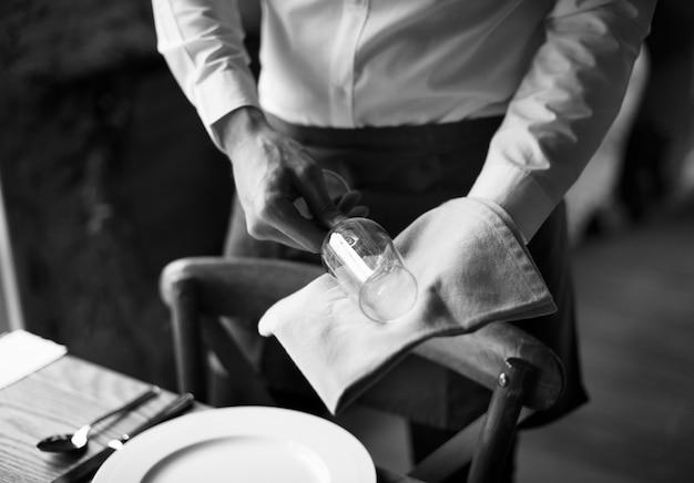 El personal del restaurante limpia el servicio de ajuste de vidrio en la mesa para la recepción