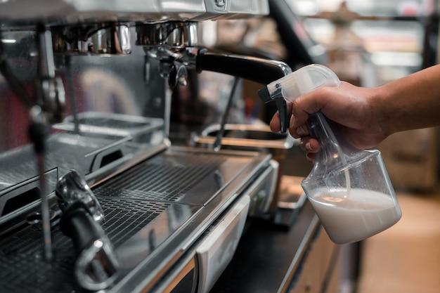 El personal está rociando una máquina de café para prevenir virus y bacterias.