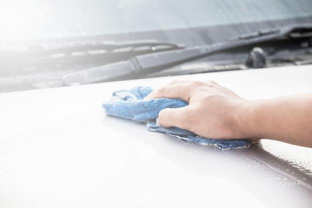 Personal de servicio de auto que limpia el parabrisas trasero del coche