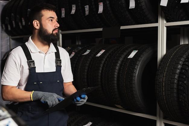 Personal de servicio hombre barbudo examinando neumáticos en un centro comercial de supermercado, piense en el comercio correcto para el tamaño de la rueda, sosteniendo la tableta de papel en las manos, comprobando