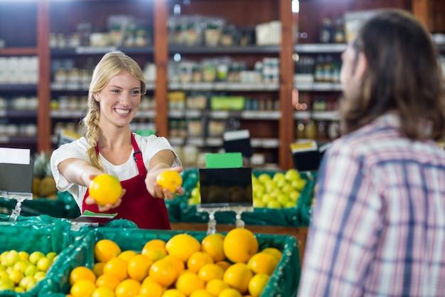 Personal sonriente ayudando a un hombre con compras
