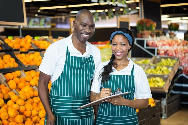 Personal sonriente escribiendo en portapapeles en la sección orgánica del supermercado