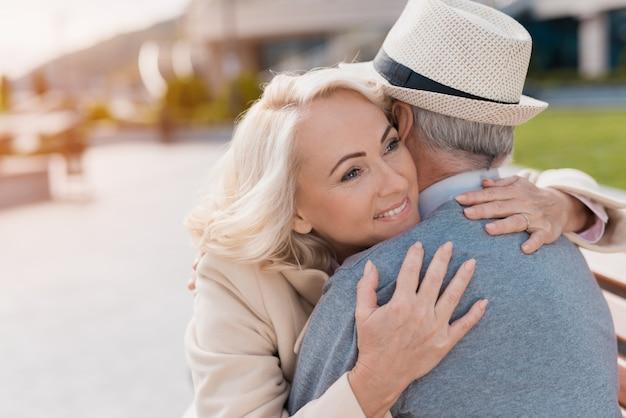 Las personas se abrazan tiernamente sentadas en un banco y sonríen felices.