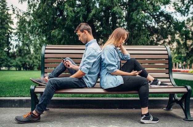 Personas adictas al teléfono, pareja en el banquillo. hombre y mujer usando sus teléfonos inteligentes en el parque de verano, adicción