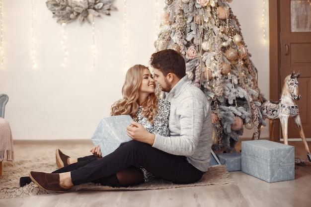 Personas en adornos navideños. hombre con un suéter gris. familia en casa.