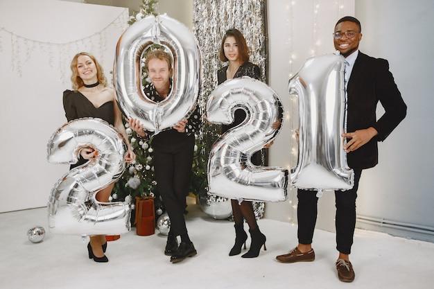 Personas en adornos navideños. hombre con traje negro. celebraciones grupales año nuevo. personas con globos 2021.
