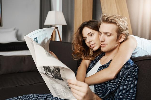 Personas adultas y atractivas en una relación sentados pasando la mañana juntos, leyendo periódicos y amándose unos a otros. él entró en su vida y ella no recuerda cómo es vivir sin él.