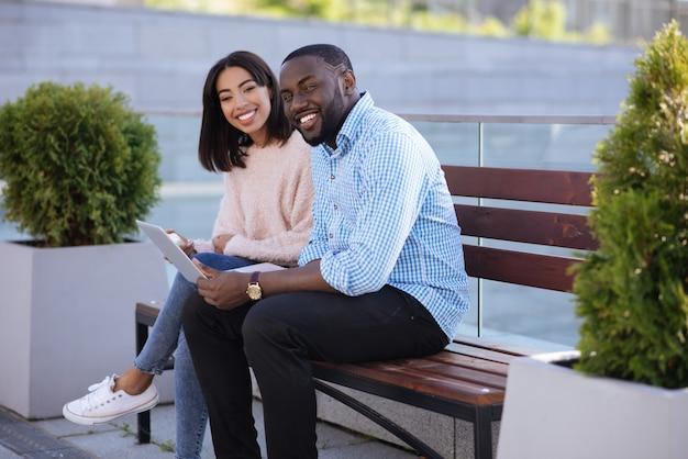 Personas alegres e innovadoras atractivas que pasan algún tiempo al aire libre y eligen artículos para comprar mientras usan una computadora portátil
