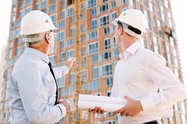 Personas de ángulo bajo con cascos mirando el diseño de andamios