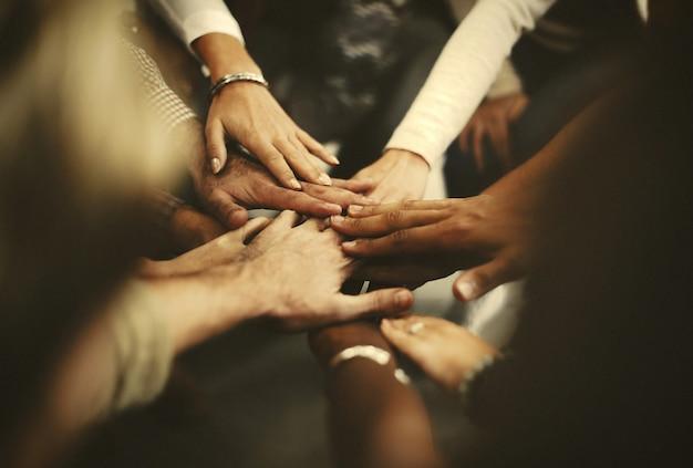 Personas apilando las manos como un equipo.
