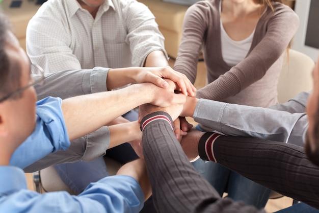 Personas apilando las manos sobre fondo claro