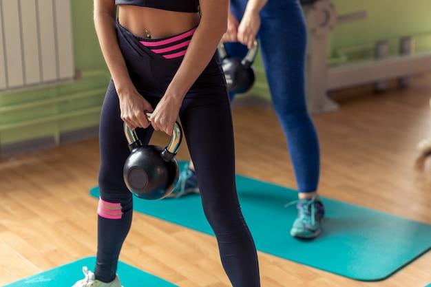 Personas aptas que pesan pesas rusas en el gimnasio