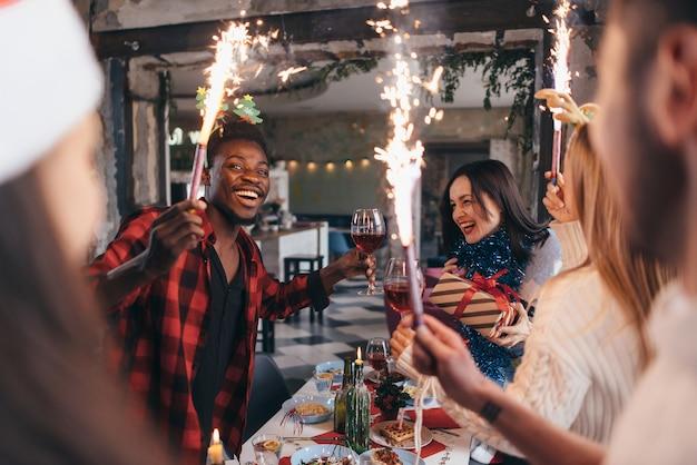 Personas brindando con champán celebrando con bengalas y mirándose sonriendo.