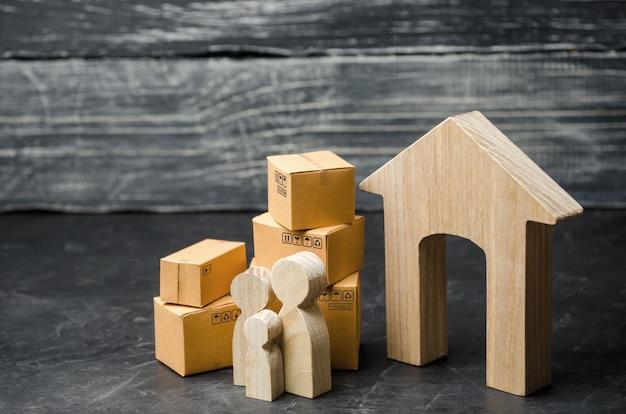 Personas con cajas de cartón están cerca de la casa. el concepto de mudarse a otra casa.