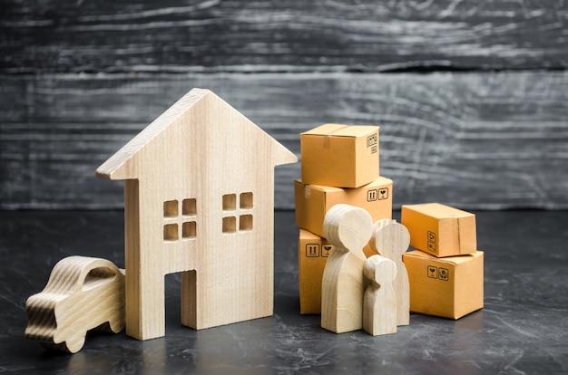 Personas con cajas de cartón están cerca de la casa. transporte de bienes y bienes.