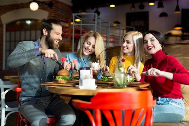 Las personas cenan juntas en una mesa en un café. amigos felices comen hamburguesas y beben cócteles en el restaurante.