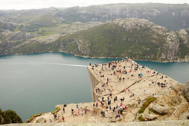 Personas en la cima del acantilado preikestolen en noruega