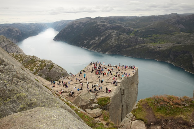 Personas en la cima de la roca preikestolen en noruega