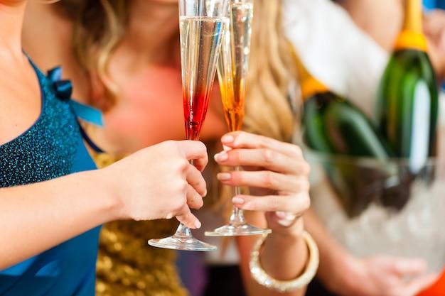 Personas en el club o bar bebiendo champaña