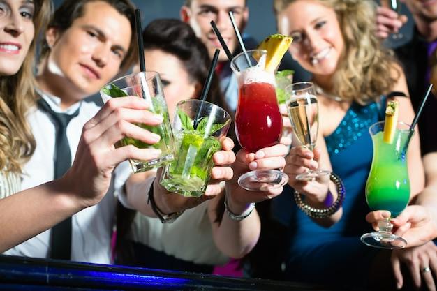 Personas en el club o bar bebiendo cócteles