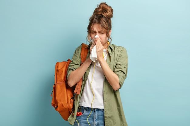Personas, concepto de enfermedad. enferma mujer de cabello oscuro estornuda en pañuelo, lleva mochila