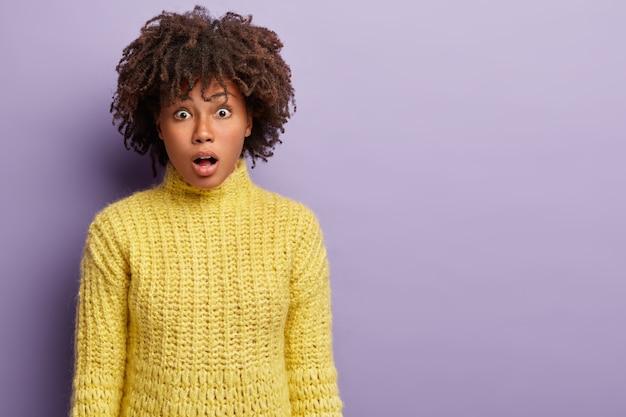 Personas, concepto de expresiones faciales. estupefacta modelo femenina de piel oscura abre la boca, expresa conmoción, escucha las malas noticias más recientes, viste ropa amarilla, aislada sobre una pared púrpura