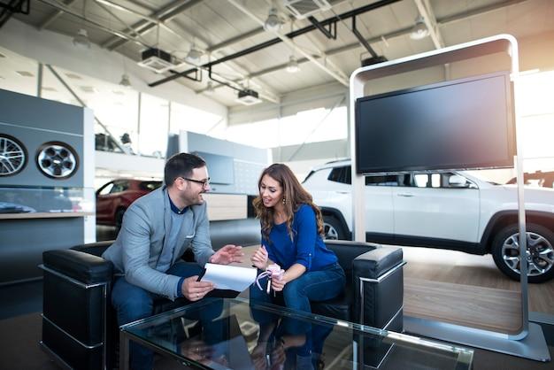 Personas en el concesionario de vehículos comprando un coche nuevo