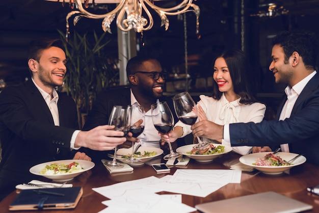 Las personas con copas de vino descansan en un restaurante.