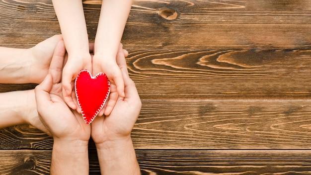 Personas con un corazón rojo en manos con espacio de copia