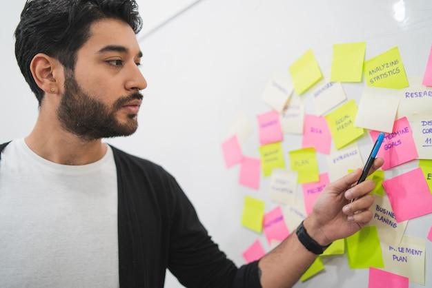 Personas creativas que se encuentran en la oficina y usan notas para publicar