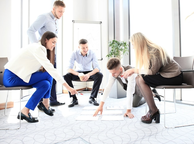Personas creativas que miran el plan del proyecto presentado en el piso. asociados de negocios discutiendo el nuevo plan de proyecto en la oficina moderna.