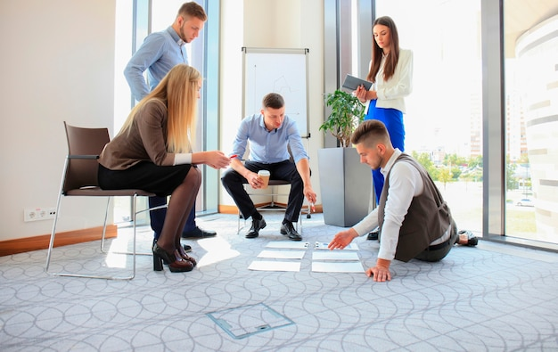 Personas creativas que miran el plan del proyecto presentado en el piso. socios comerciales discutiendo el plan del proyecto en la oficina moderna.